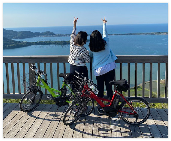 Two Japanese women looking out over a lake doing the peace gesture